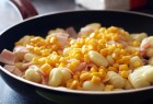 Preparing healthy gnocchi with ham and corn
