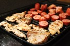 Grill full of chicken steaks and sausages